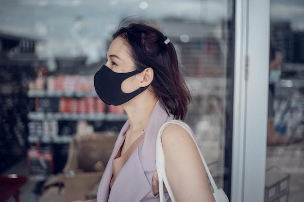 Aziatisch wijfje met medisch masker op de stadsstraat. leven tijdens covid-19 pandemie.