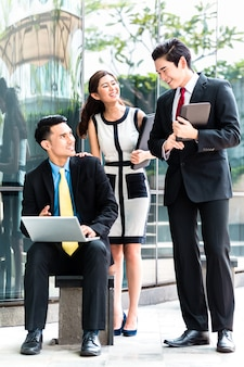 Aziatisch zakenlui die buiten aan laptop werken