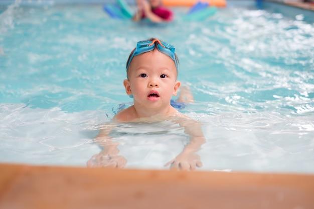 Aziatische 1 jaar oude peuter jongenskind slijtage zwembril leren om te zwemmen