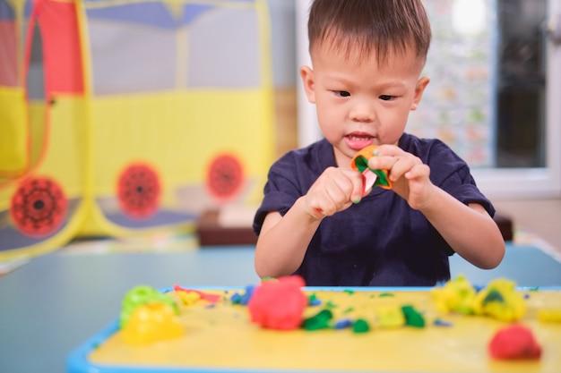 Aziatische 2-3 jaar oud peuter jongenskind dat pret heeft die kleurrijke boetseerklei speelt / deeg thuis speelt, educatief speelgoed voor jong geitje
