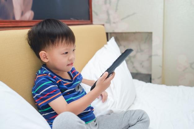 Aziatische 3 - 4 jaar oude peuter jongenskind zittend in bed met de afstandsbediening van tv en thuis televisie kijken in de slaapkamer
