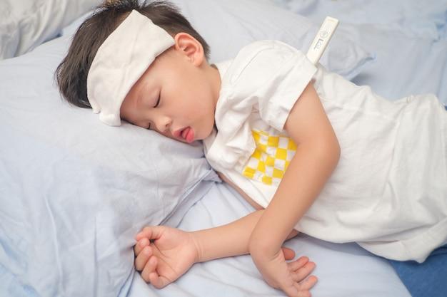 Aziatische 3-4 jaar oude peuterjongen krijgt hoge koorts liggend op bed met koud kompres, nat washandje op voorhoofd om pijn te verlichten