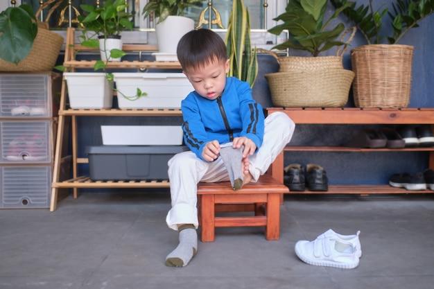 Aziatische 3 jaar oude peuter kleuterschool kind zit in de buurt van schoenenrek in de buurt van de voordeur van zijn huis en concentreert zich op het aantrekken van zijn eigen sokken