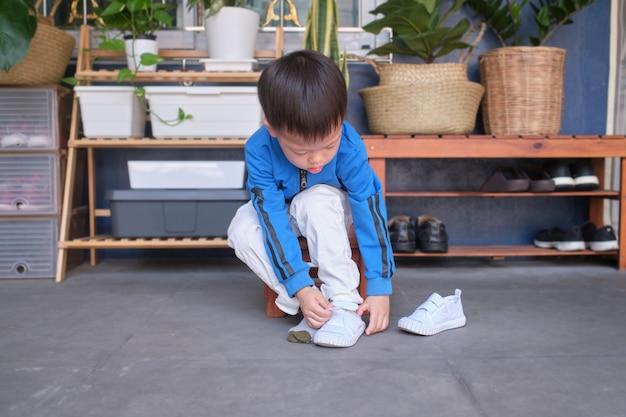 Aziatische 3 jaar oude peuter kleuterschool kind zit in de buurt van schoenenrek in de buurt van de voordeur van zijn huis en concentreert zich op het aantrekken van zijn witte schoenen / sneakers