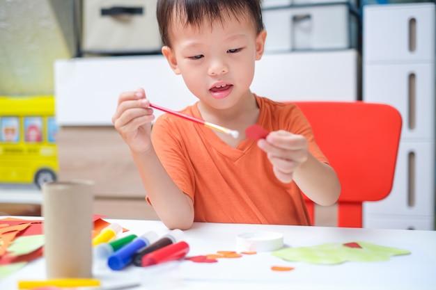 Aziatische 3-jarige peuterjongen geniet thuis van het gebruik van lijm om kunst te doen, leuk papier en lijmambachten voor peuters, kinderkunstproject