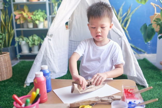 Aziatische 4-jarige kleuterjongen geniet van het thuis knutselen, doe-het-zelf speelgoed voor kinderen van recyclable materials concept