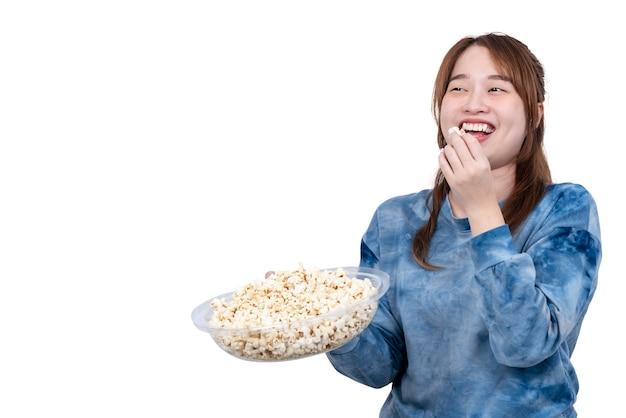 Aziatische aantrekkelijke jonge dikke vrouw die een kom popcorn glimlacht en geniet van het eten van popcorn