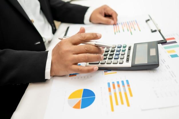 Aziatische accountant die en financiële rapportenprojectboekhouding met grafiek werkt analyseert.