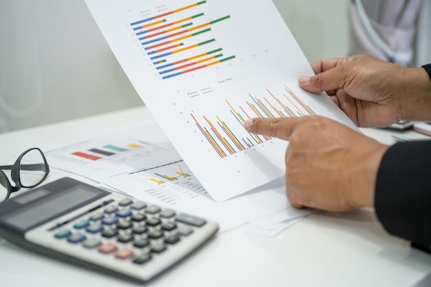 Aziatische accountant werkt en analyseert financieel rapportproject