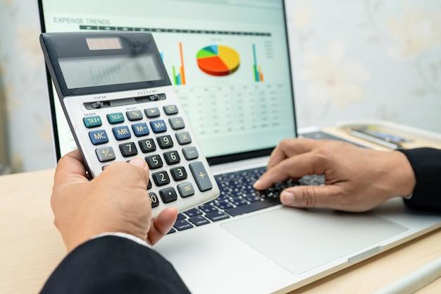 Aziatische accountant werkt en analyseert project voor financiële rapporten analyzing