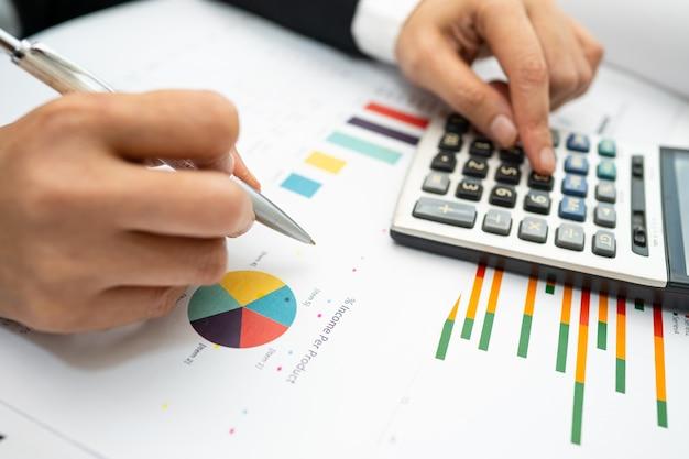 Aziatische accountant werkt projectboekhouding met grafiek en rekenmachine.