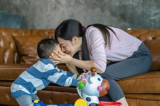 Aziatische alleenstaande moeder en zoon spelen samen met speelgoed wanneer ze in een loft wonen voor zelfstudie