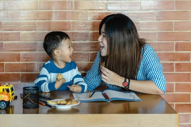 Aziatische alleenstaande moeder en zoon tekenen en eten samen een koekje als ze in een loft wonen