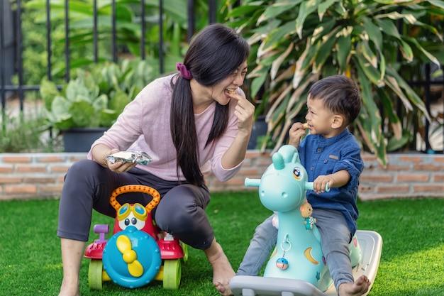 Aziatische alleenstaande moeder met zoon speelt met speelgoed en eet samen als ze in het voorste gazon wonen