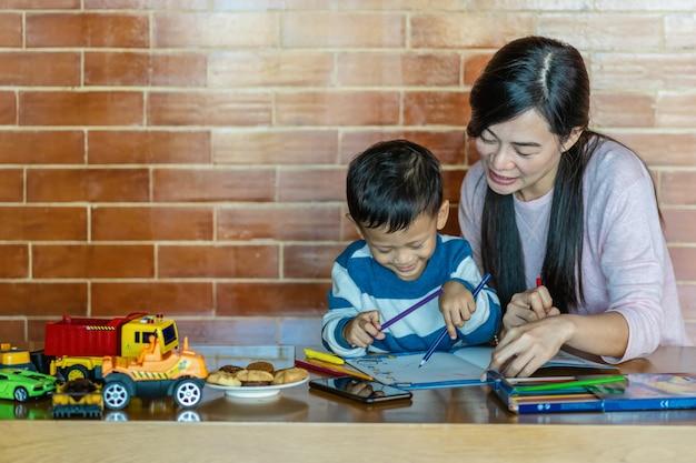 Aziatische alleenstaande moeder met zoon tekenen samen in loft-huis voor zelfstudie of thuisschool