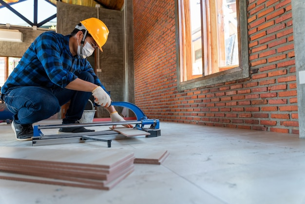 Aziatische ambachtelijke tegelzetter op bouwplaats, werknemer snijdt een grote plaat tegel tijdens de bouw van een huis, snijapparatuur voor vloertegels
