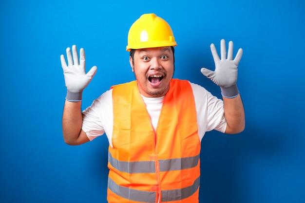 Aziatische arbeider die een helm draagt, ziet er geschokt uit als hij het nieuws hoort terwijl hij zijn mond met zijn handen sluit