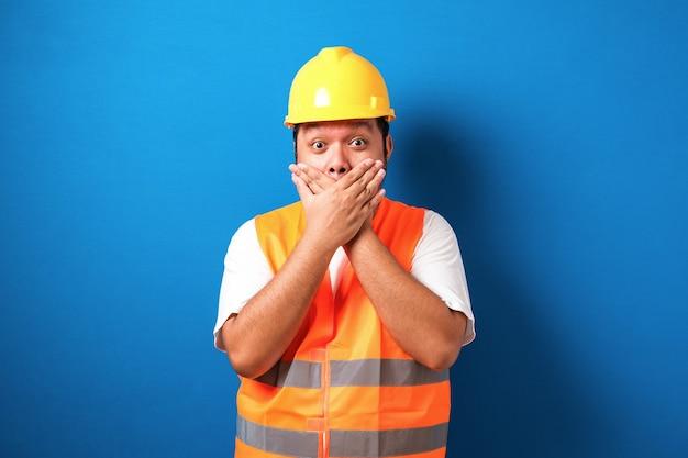 Aziatische arbeider die een helm draagt, ziet er geschokt uit als hij het nieuws hoort terwijl hij zijn mond sluit