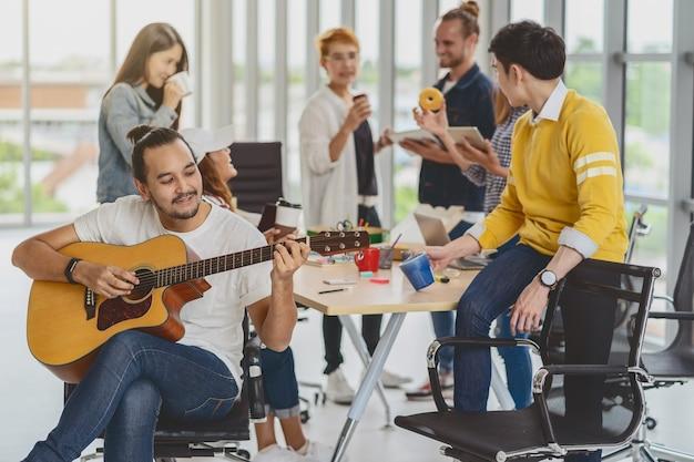 Aziatische arbeider die gitaar speelt over de groep aziatische en multi-etnische zakenmensen