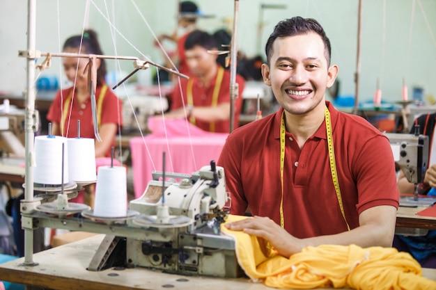 Aziatische arbeider in textielfabriek naaien die industrieel naaien gebruiken