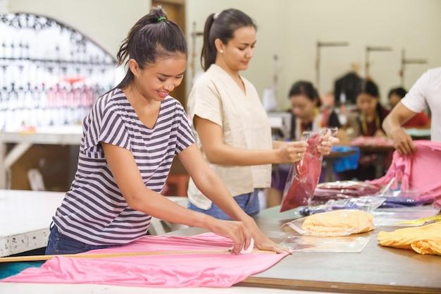 Aziatische arbeiders die een stof markeren en hun product verpakken