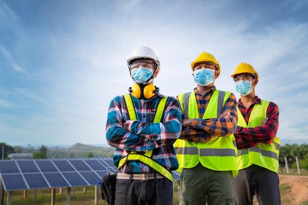 Aziatische arbeiders dragen beschermende maskers voor de veiligheid op de bouwplaats elektriciteit zonne-energie-industrie, natuurlijke energie, nieuw normaal