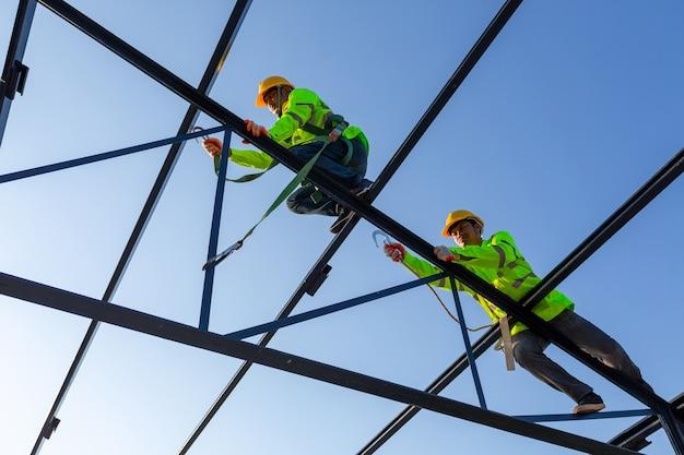 Aziatische arbeiders dragen veiligheidshoogte-uitrusting om een stalen dakconstructie op de bouwplaats te bouwen.