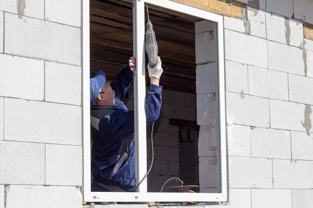 Aziatische arbeiders installeren ramen bij de bouw en renovatie van huizen