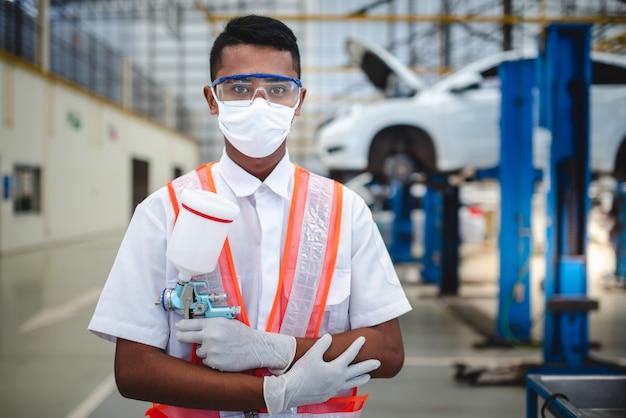 Aziatische arbeiders staan met een spuitpistool in beschermende kleding