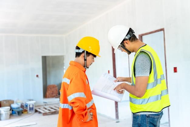 Aziatische architect en ingenieur geven instructies aan zijn voorman op klembord die op de bouwplaats werken