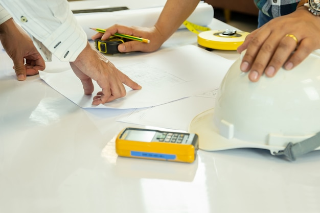 Aziatische architectuer die aan planhanden werken die op bluepring schets richten.