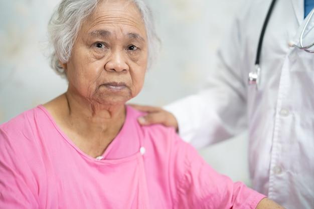 Aziatische arts die aziatische senior of oudere oude damevrouw aanraakt met liefde, zorg, helpen, aanmoedigen en empathie op de verpleegafdeling, gezond sterk medisch concept.