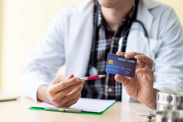 Aziatische arts die een creditcard toont aan patiënt. gezondheidszorg en verzekering concept.