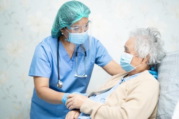 Aziatische arts die een gelaatsscherm en pbm draagt, past nieuwe norm aan om te controleren of de patiënt covid-19 coronavirus beschermt.