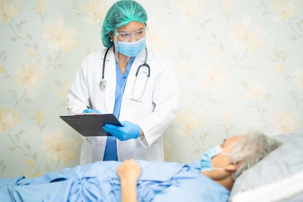 Aziatische arts die een gelaatsscherm en ppe-pak draagt om te controleren of de patiënt covid-19 coronavirus beschermt.