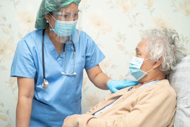Aziatische arts die een gelaatsscherm en ppe-pak draagt om te controleren of de patiënt de veiligheidsinfectie covid-19 coronavirus beschermt.