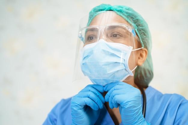 Aziatische arts die een gezichtsscherm en een pbm-pak draagt om het covid-19 coronavirus te beschermen.