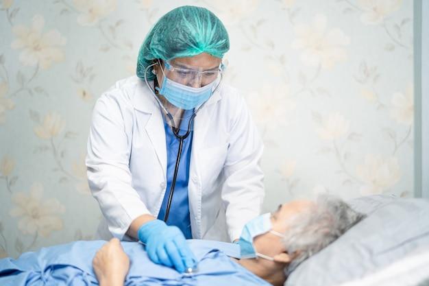 Aziatische arts die gelaatsscherm en pbm draagt past nieuw normaal aan om de patiënt te beschermen beschermt covid-19