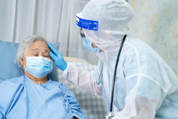 Aziatische arts die gelaatsscherm en ppe-pak draagt