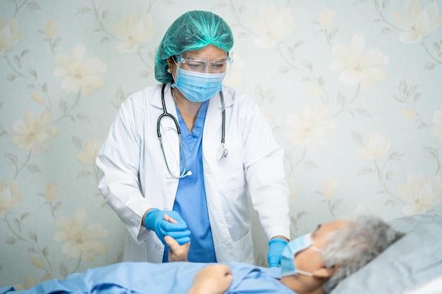 Aziatische arts die gezichtsscherm en pbm-pak draagt om het covid-19 coronavirus te beschermen.