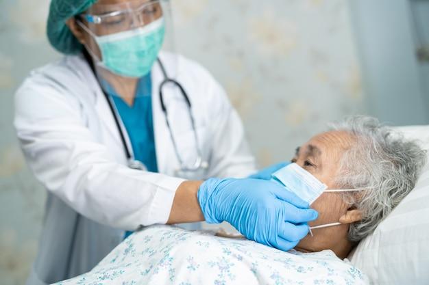 Aziatische arts die gezichtsscherm en pbm-pak draagt om te controleren of de patiënt het covid-19 coronavirus beschermt.
