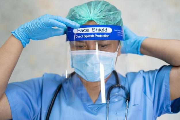 Aziatische arts die gezichtsscherm en pbm-pak draagt ter bescherming van het covid-19 coronavirus.