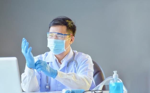 Aziatische arts die medische masker en handschoenen draagt. geïsoleerd met grijze muur op zoek hand.