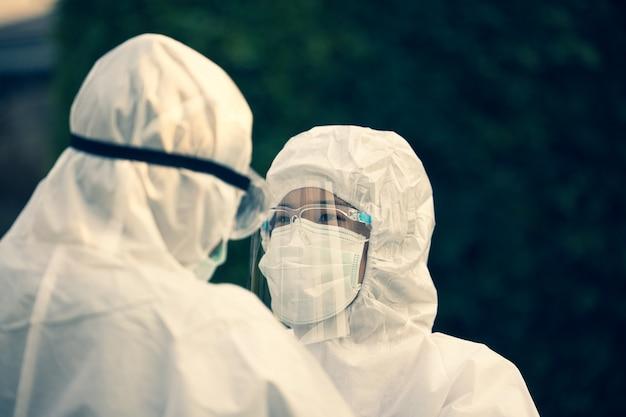 Aziatische arts die ppe-kostuum en gezichtsmasker in het ziekenhuis of buiten draagt.