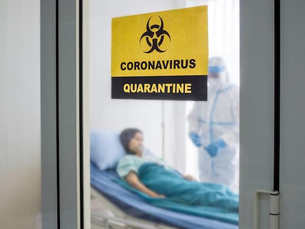 Aziatische arts draagt ppe-pak met n95-masker en gelaatscherm, behandelt coronavirus-geïnfecteerde patiënt in kamer met negatieve druk, label met quarantaine-waarschuwingsgebiedteken.