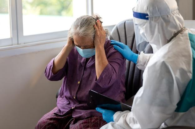 Aziatische arts draagt ppe-pak praat met oude vrouwelijke patiënt over ziektesymptoom, gezondheidscontrole bij ouderen, ze dragen een chirurgisch masker met comfort en aanmoediging voor ouderen.
