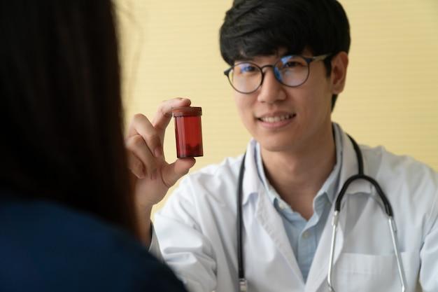 Aziatische arts met een stethoscoop en uniform met een medicijnfles en legt de medicinale eigenschappen van de patiënten uit.