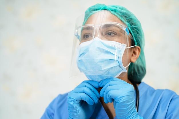 Aziatische arts met gezichtsscherm en pbm-pak nieuw normaal om te controleren of de patiënt de veiligheid van de infectie covid-19 coronavirus-uitbraak op de quarantaineverpleegkundige ziekenhuisafdeling beschermt.