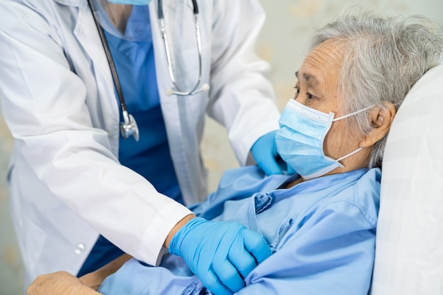 Aziatische arts met gezichtsscherm en pbm-pak nieuw normaal om te controleren of de patiënt de veiligheidsinfectie covid-19 beschermt