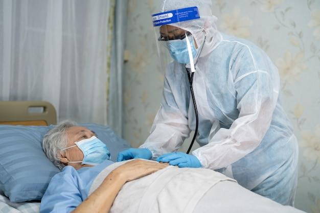 Aziatische arts met gezichtsscherm en ppe-pak nieuw normaal om te controleren of de patiënt de veiligheidsinfectie beschermt covid-19 coronavirus-uitbraak op de verpleegafdeling van het quarantaineziekenhuis.